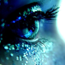 closeup of a single eye lined with blue glitter